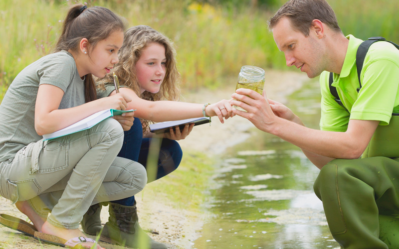 Girls and older man examining water sample